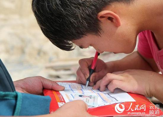 Cui Qingtao signs for the packet containing his acceptance letter from Peking University, July 22, 2018.  (Photo/people.cn)