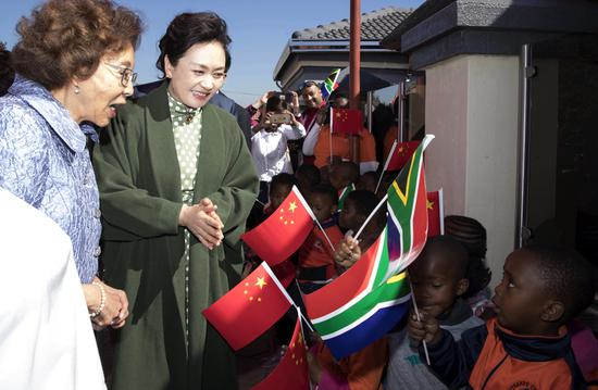 Peng Liyuan, the wife of President Xi Jinping and a UNESCO special envoy, and South African first lady Tshepo Motsepe visit Uthando Day Care Preschool in a suburb of Pretoria, South Africa, on Tuesday. (Photo: Xinhua/Wang Ye)