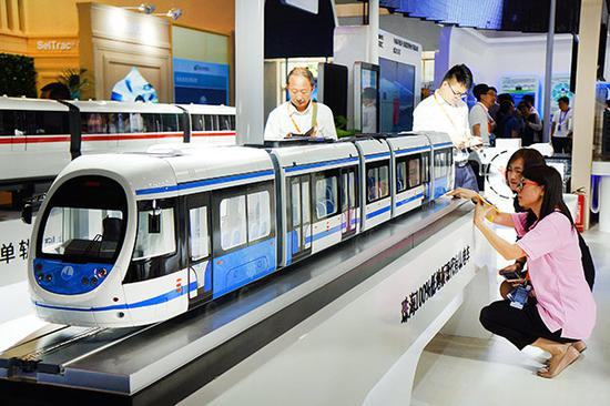 Visitors look at the latest models of urban rail trains shown at the International Urban Rail Exhibition in Beijing. (Photo/Xinhua)
