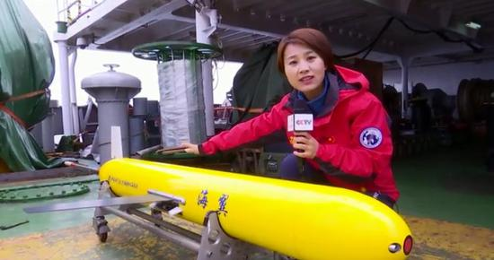 CCTV's reporter explains different parts of the underwater glider at a close range. (CCTV Photo)