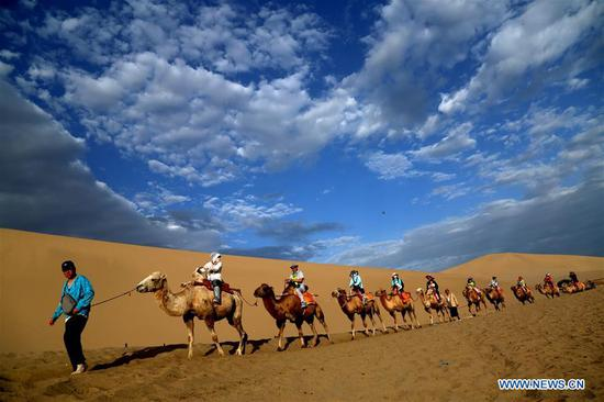 Tourists visit Mingsha Mountain and Crescent Spring scenic spot in Dunhuang