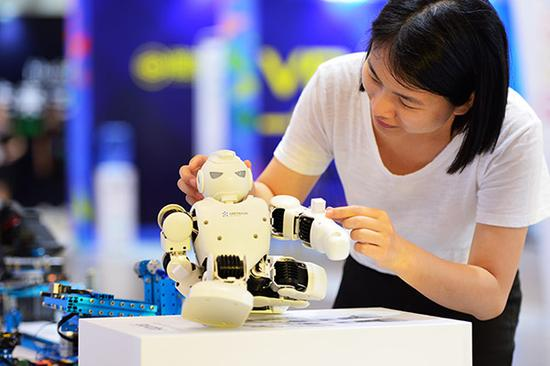 A visitor plays with a small robot at a science and cultural innovation exposition held in the China (Fujian) Pilot Free Trade Zone. (Photo/Xinhua)