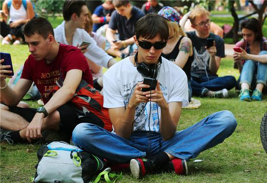 People use their mobile devices at a park in Moscow. (PHOTO PROVIDED TO CHINA DAILY)