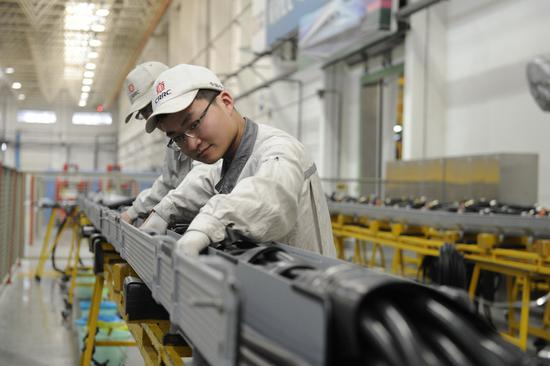 CRRC employees operate an assembly line of the company in Qingdao, Shandong province. (Photo by Zhang Jingang/For China Daily)