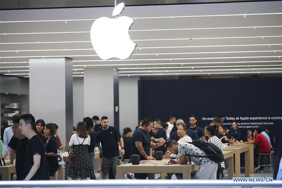 Customers select products at an Apple store in New York, the United States, Aug. 2, 2018. U.S. tech giant Apple became the first American company that saw its market cap hit 1 trillion U.S. dollars in the U.S. history after its shares rose 2.8 percent to a session high of 207.05 dollars around midday trading on Thursday. (Xinhua/Wang Ying)