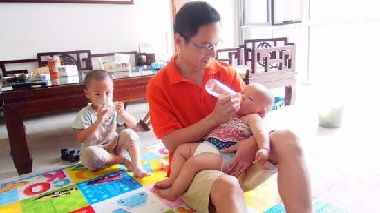 A stay-at-home dad takes care of his young children in Jinan, Shandong Province. (Provided to China Daily)