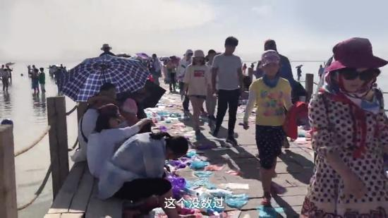Screenshot of the video showing people walking on the pier with the floor covered in plastic bags and shoe covers. (Photo/CGTN)