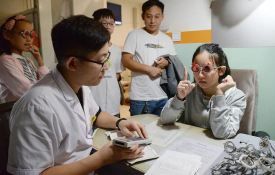 A primary school student gets a vision test in Handan, Hebei Province, during the summer holiday. Summer, especially the days before school resumes, is a peak season for such tests. (Hao Qunying/For China Daily)