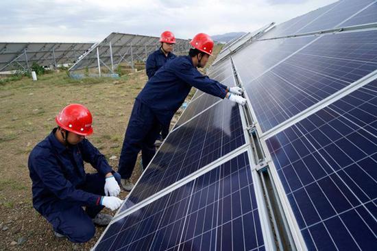 Technicians check solar power generation facilities in Datong, Shanxi province. (Photo by YU JIARUI FOR CHINA DAILY)