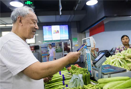 A man scans a QR code to pay for vegetables in Hangzhou, Zhejiang Province. (Xu Kangping/For China Daily)