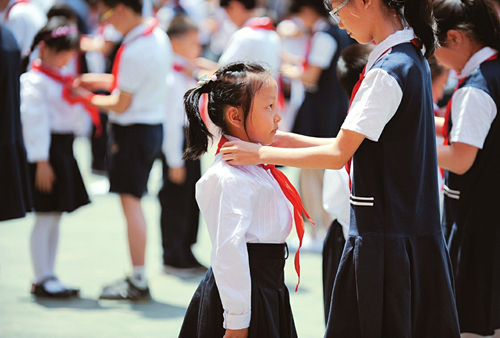 A student from sixth grade adjusts a red scarf on a first grade student at Shanxi Experimental Primary School, Taiyuan, May 31. More than 400 students in first grade put on red scarves for the day –– a symbol of them joining the Young Pioneers of China movement, as part of the upcoming International Children's Day on June 1. (Photo/Shanxi Daily)