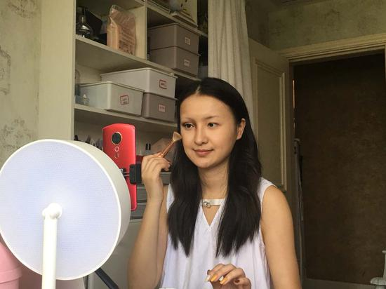 He Yuhong does her makeup. She attempts to copy Mona Lisa, subject of Leonardo Da Vinci's masterpiece. /CGTN Photo