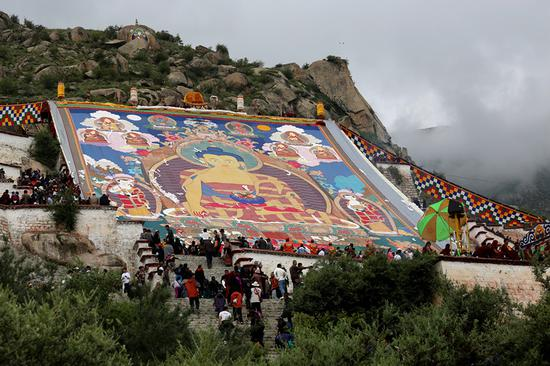 People celebrate the unrolling of a thangka-a giant religious silk painting-at Drepung Monastary in Lhasa, capital of the Tibet autonomous region, at the start of the Yogurt Festival on Saturday. (PALDEN NYIMA/CHINA DAILY)