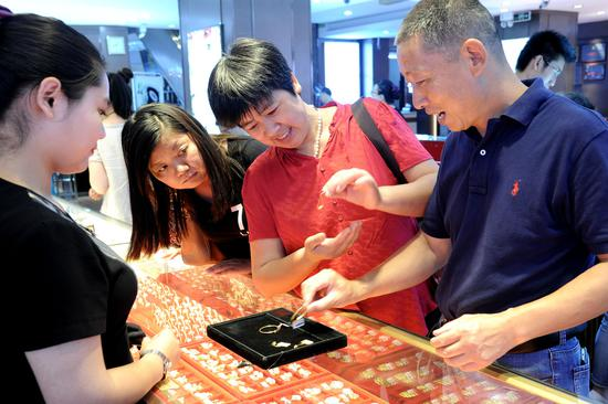 Consumers browse gold ornaments at a jewelry store in Suzhou, Jiangsu Province. (Photo for China Daily by Wang Jianzhong)