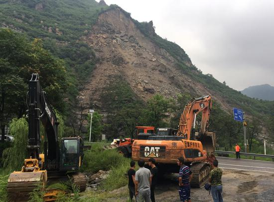 Workers prepare for road clearing work at a landslide site in Beijing's Fangshan district on Saturday. (Photo by WANG JING/CHINA DAILY)