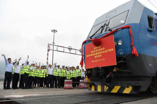 Workers cheer the launch of a transshipment link connecting China and Singapore at Chongqing on Sept. 25, 2017. The link is part of the corridor comprising railway and sea lines that shorten cargo transport to the ASEAN region by 20 days. (Photo/Xinhua)