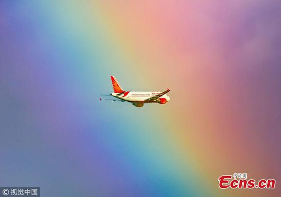 Stunning photo shows plane flying into rainbow