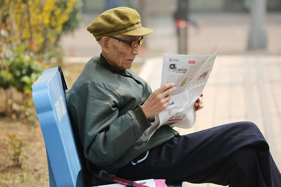 Zhou Zhifu, the late army officer, reads a newspaper in a garden at the sanatorium where he spent his post-retirement life. (Photo provided to China Daily)