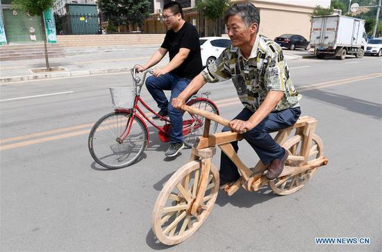 55岁的农民和他在甘肃的木制自行车