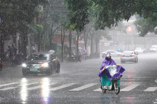 A woman rides an electric bike in the rain in Shanghai on August 16, 2018. (Photo/Shine.cn)