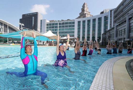 Retirees practice yoga in a swimming pool at a gym in Hangzhou, Zhejiang Province. (Photo by Lin Yunlong / For China Daily)