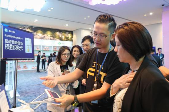 Hong Kong residents try Tencent's new online service to apply for mainland's bank cards. (Photo/China News Service)