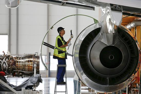 An employee checks an engine at the A320 family final assembly line of the Airbus factory in Tianjin. (Photo provided to China Daily)