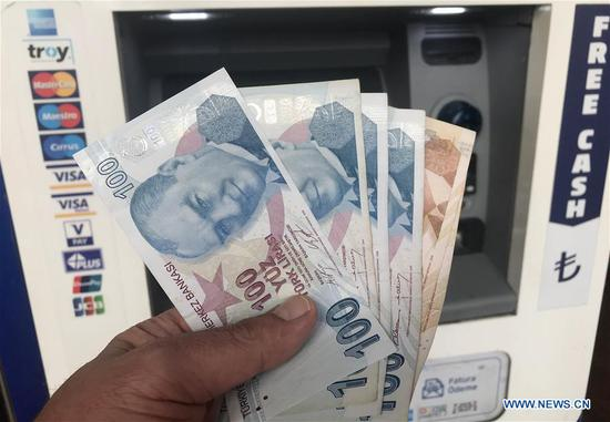 A man counts Turkish lira in Istanbul, Turkey, on Aug 14, 2018. Turkish President Recep Tayyip Erdogan announced Tuesday to boycott US electronic products amid an ongoing and deepening rift between the two NATO allies over a number of issues. Erdogan reiterated that the recent plunge of Turkish lira and stocks was caused by an economic attack by U.S. President Donald Trump and his administration. (Photo/Xinhua)
