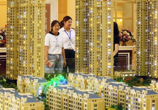 A saleswoman (center) talks with customers at a real estate sales office in Huai'an, Jiangsu Province. (Photo/ China News Service)