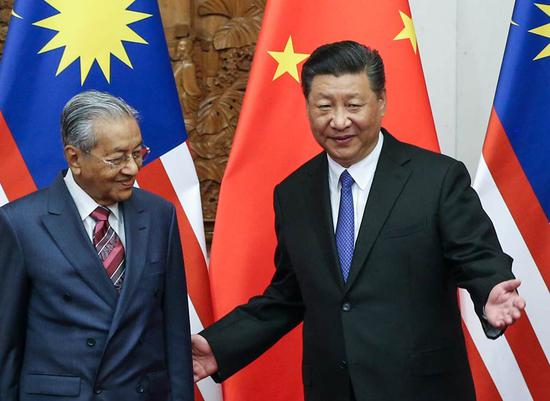 President Xi Jinping greets Malaysian Prime Minister Mahathir Mohamad at the Great Hall of the People in Beijing on Monday. During his talks with Mahathir, Xi said the two countries should be dedicated to raising the representation of developing countries in global affairs. WU ZHIYI / CHINA DAILY