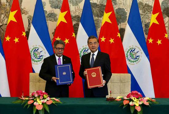 Chinese State Councilor and Foreign Minister Wang Yi and EL Salvador Foreign Minister Carlos Castaneda sign a joint communique on the establishment of diplomatic relations in Diaoyutai State Guesthouse in Beijing on Tuesday. (Photo by Xu JingXing/China Daily)