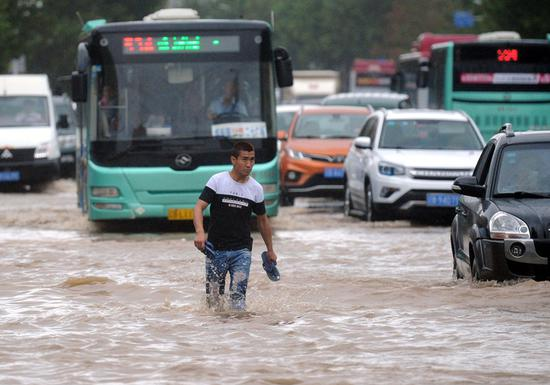 A man walks through a flooded street in Dalian, Liaoning Province, on Monday. Typhoon Rumbia brought torrential rains and caused severe flooding in the city. (LYU WENZHENG/FOR CHINA DAILY)