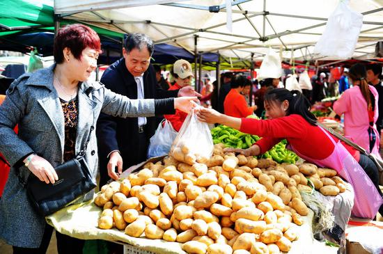 Consumers buy vegetables at a market in Qingdao, East China's Shandong Province. (Photo by Yu Fangpin /For China Daily)
