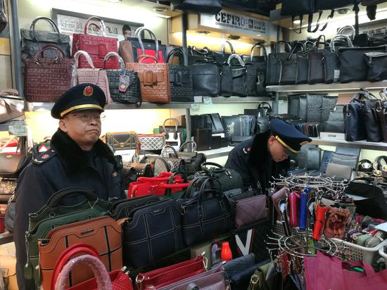 Officers from the Dongcheng district branch of the Beijing Administration for Industry and Commerce launch investigations during Spring Festival in an effort to combat the sale of counterfeits. (Photo by Pei Qiang and Niu Jing/for China Daily)