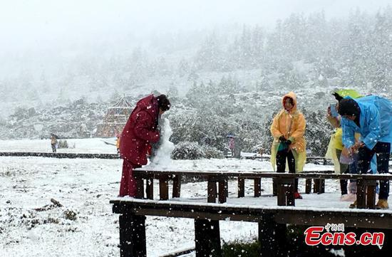 Visitors enjoy view of snow at Daocheng Yading scenic spot in Ganzi Tibetan Autonomous Prefecture of southwest China's Sichuan province on September 20, 2016. (File photo/China News Service)