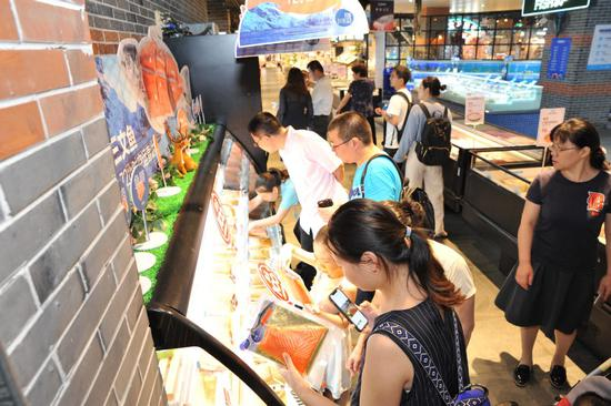 Consumers pick imported salmon fillets from a freezer at a Hema Fresh store in Shanghai. (Photo provided to chinadaily.com.cn)