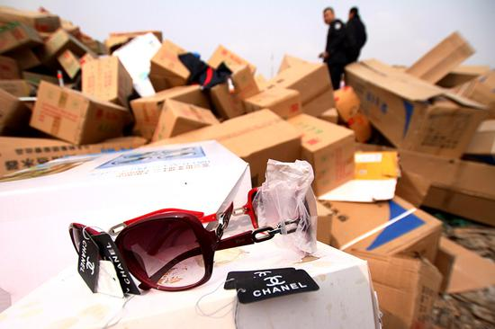 Officers from the Chengguan district branch of the Lanzhou Administration for Industry and Commerce in Gansu province destroy counterfeit goods they seized last year. (Photo by Pei Qiang and Niu Jing/for China Daily)