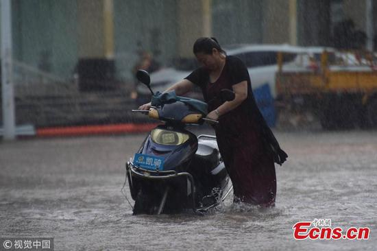 Rainstorm slows traffic on flooded streets in Qionghai City