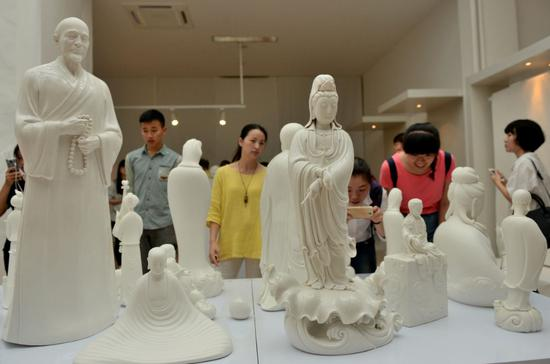 Visitors check out ceramic products made in Dehua county, Fujian province. (Photo provided to China Daily)