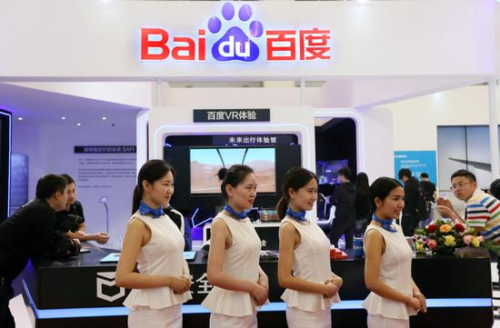 Baidu employees pose for a photograph at the company's booth during a high-tech exhibition in Beijing. (Photo by A Qing/For China Daily)