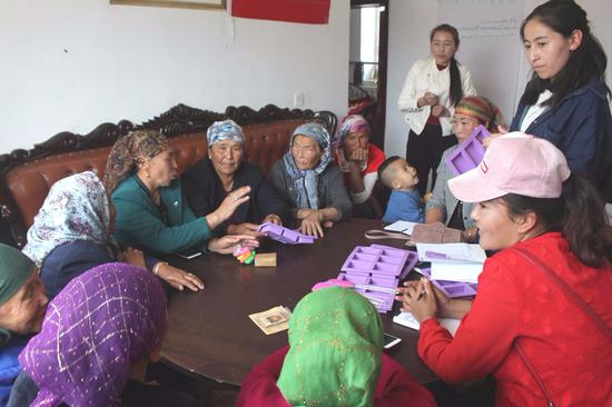 Members of the workshop attend a group meeting. (China Daily)