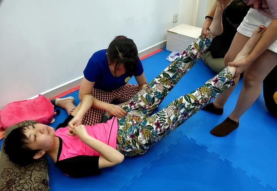 Rett syndrome patient Sze Ka-yan receives mobility therapy. (Photo/China Daily)