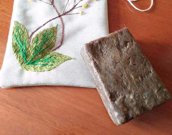 A piece of black soap and its packing bag made by Kazakh women in a soap-making workshop in Qinghe county, in the Xinjiang Uygur autonomous region. (Photo/China Daily)
