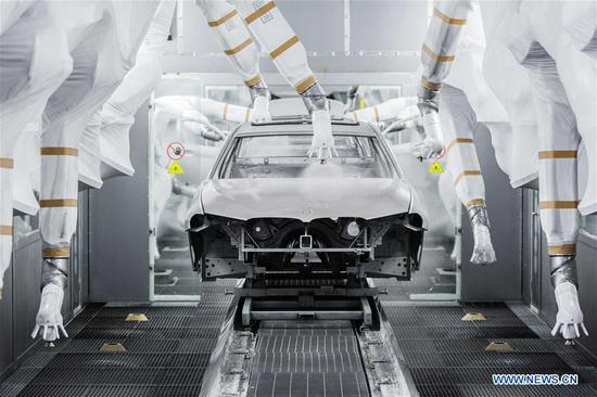 This undated photo shows a car being painted by robots at a factory of BMW in Shenyang, capital of northeast China's Liaoning Province. (Xinhua)