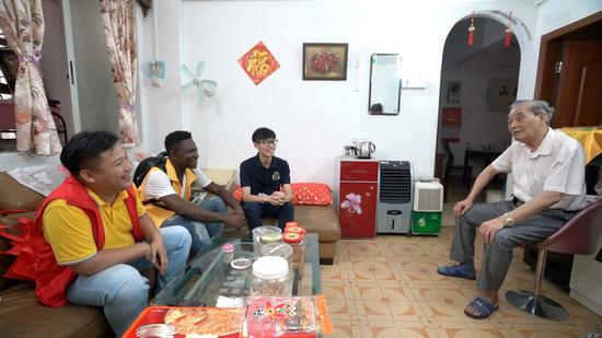 Michel and other Chinese social workers visiting a local senior.  /CGTN Photo