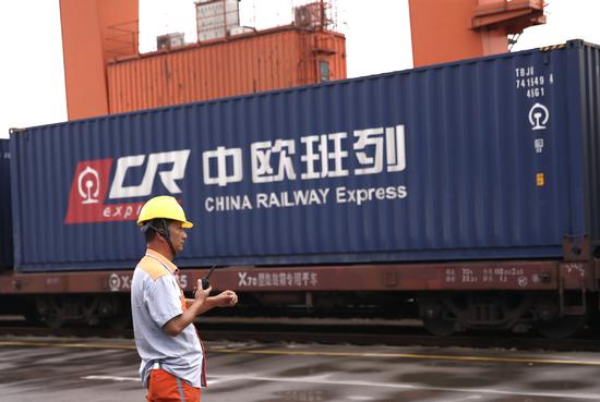 A railway employee supervises a freight train from Europe to China under the China Sino Euro Cargo Railway program. (Photo by Zou Hong / China Daily)