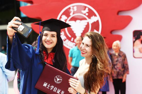 A foreign student takes a selfie at her graduation ceremony at Zhejiang University on June 28, 2018. (Photo/Xinhua)