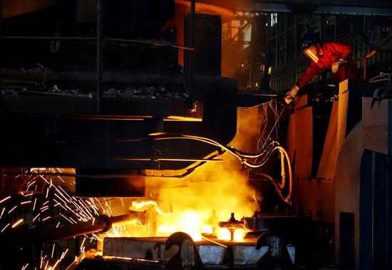 A worker tests the temperature of molten steel at a steel plant in Dalian, Liaoning province. (Photo by Liu Debin/For China Daily)