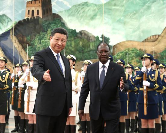 President Xi Jinping accompanies Cote d'Ivoire President Alassane Ouattara in the Great Hall of the People in Beijing on Thursday. (Photo by Feng Yongbin/China Daily)