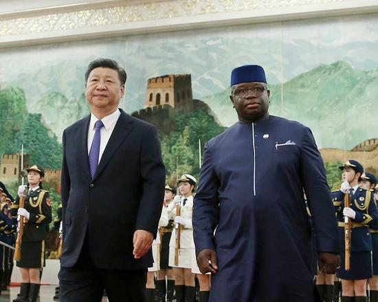 President Xi Jinping walks with Sierra Leonean President Julius Maada Bio in the Great Hall of the People in Beijing on Thursday. (Photo by Wang Zhuangfei/China Daily)